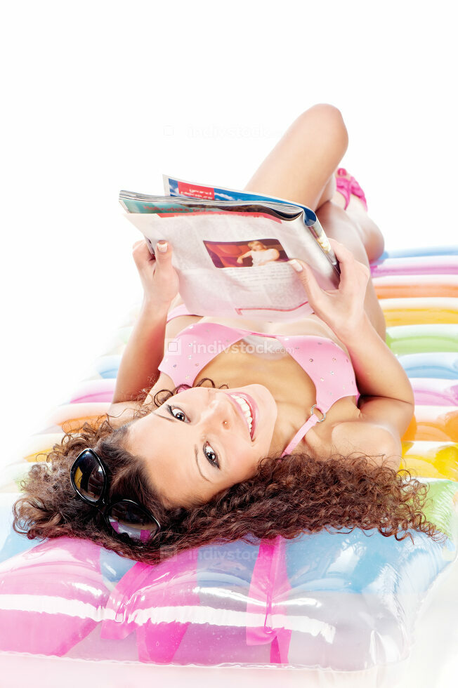 girl reading magazine on air mattress