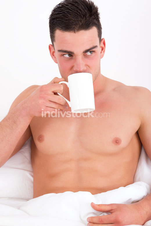 attractive man in bed drinking coffee