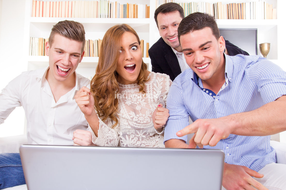 casual young group of friends watching and cheering together at