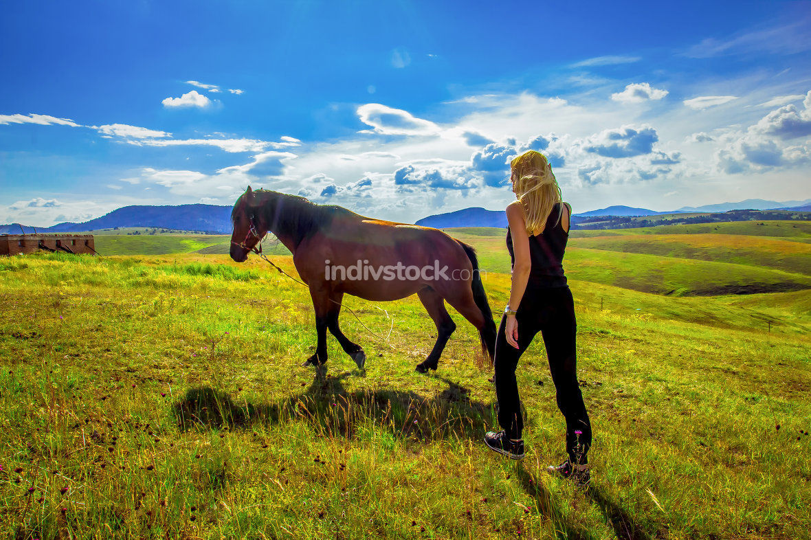 cute girl leading a horse across the meadow