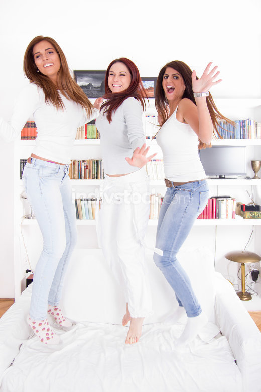 happy party girls jumping on couch
