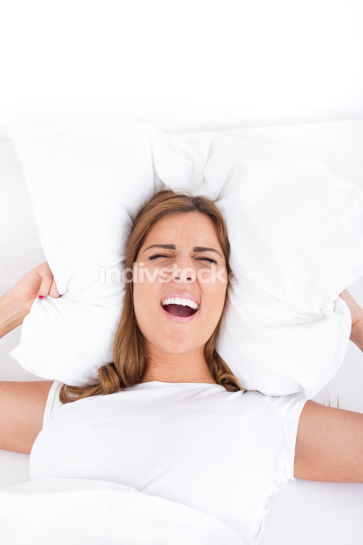 Image of irritated female lying on bed and closing her ears with