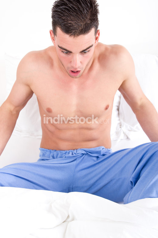 man in bed looking at his genital area having problems
