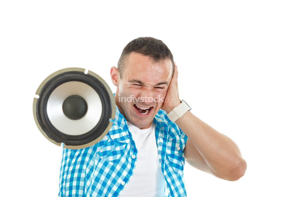 Man listening to loud music holding speaker and covering ears