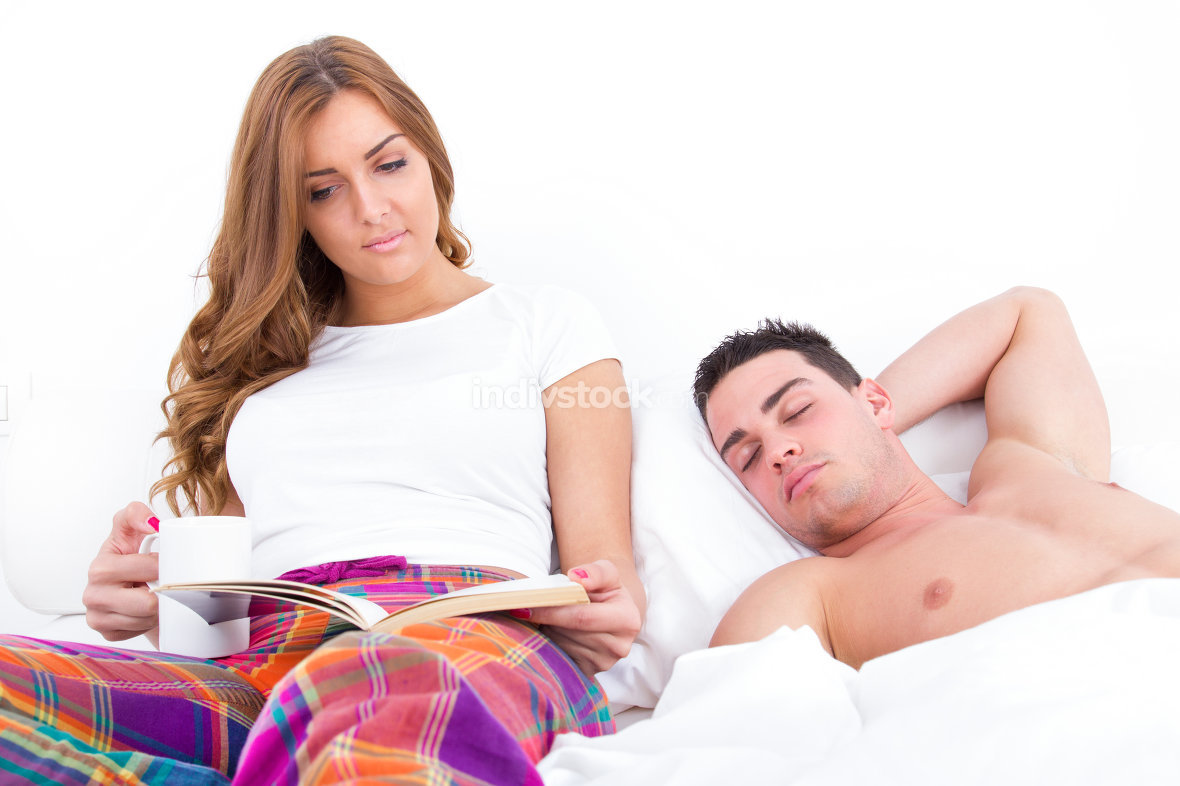 man sleeping while his girlfriend is reading in bed