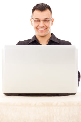 satisfied man with glasses in a black shirt looking at laptop
