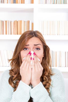 sick woman with cold and virus sneezing into tissue