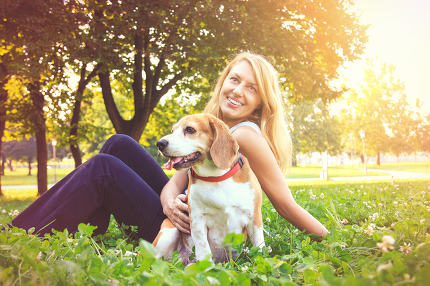 Young woman embracing her beagle puppy dog in the park