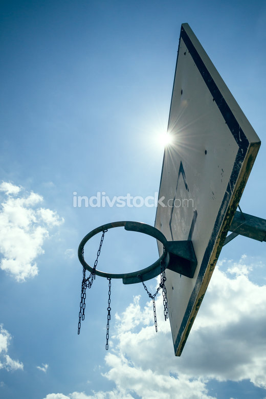 A basketball hoop from below with sun in the sky