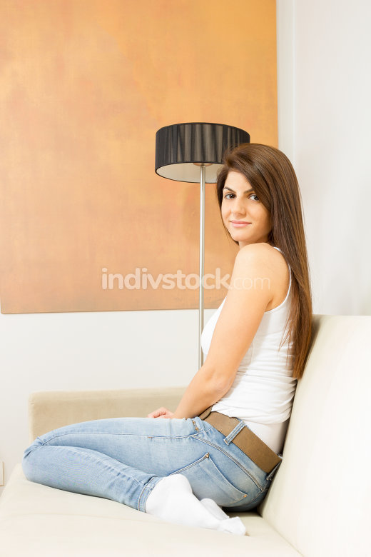 girl sitting on sofa next to lamp