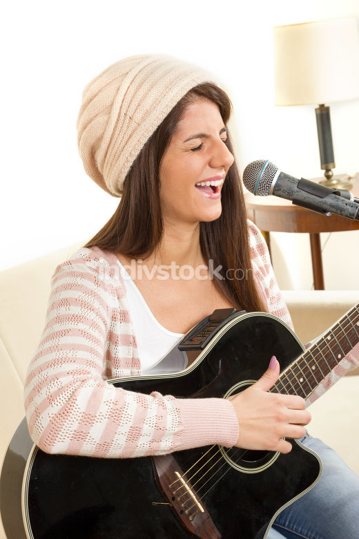 girl with a guitar singing on microphone