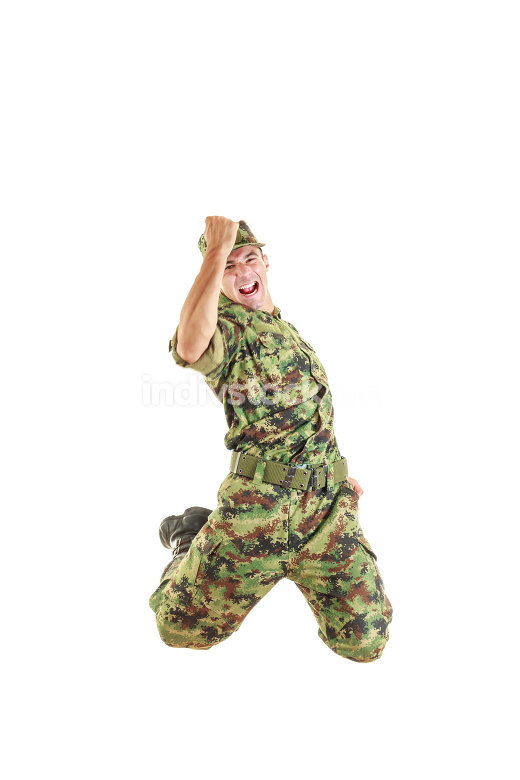 handsome soldier in green camouflage uniform and hat jumping