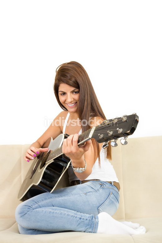 pretty girl playing guitar on the sofa