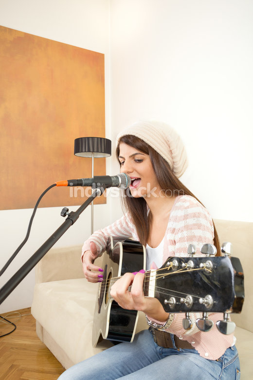 pretty girl singing and playing guitar