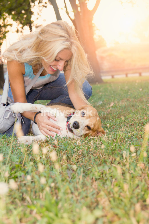 smiling blonde woman lying and playing with dog