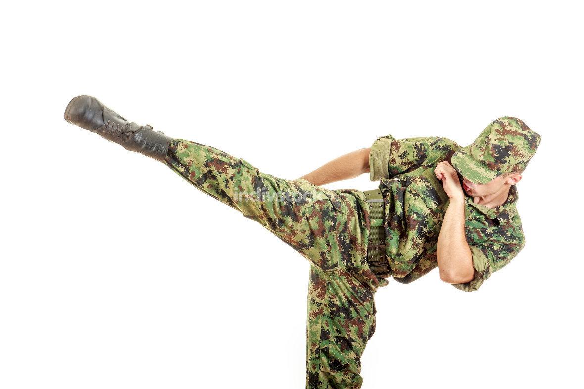 soldier in a green camouflage uniform kicking