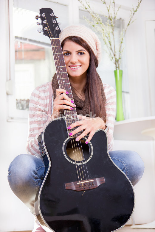 sweet young girl holding the guitar