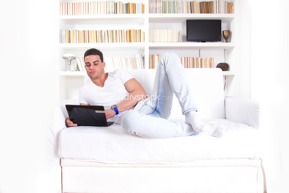 thoughtful man lying on couch at home working on laptop