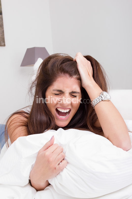 young angry woman on the bed pulling her hair and screaming