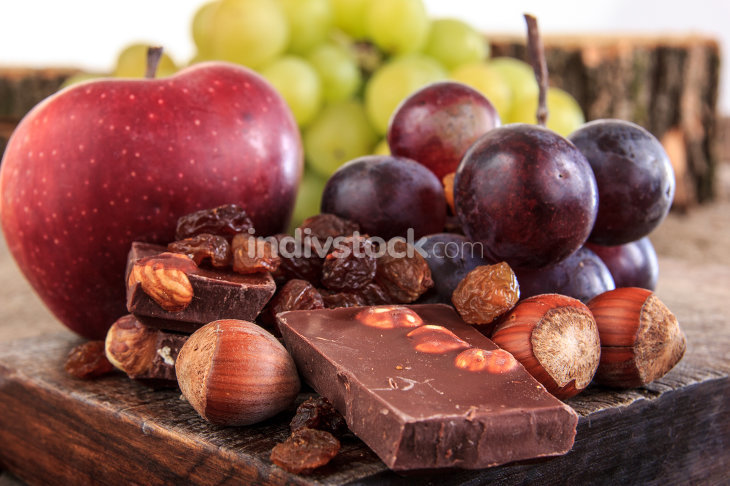 Bunch of fruit apples and grapes with nuts chocolate