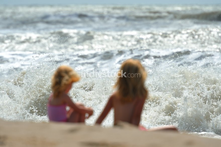 Two girls in front of the roaring surf