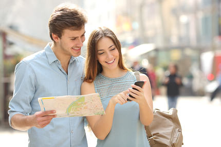 Couple of tourists consulting a city guide and smartphone gps