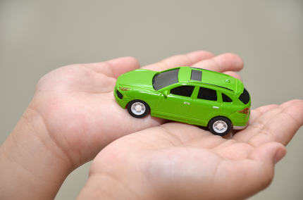 Green toy car on hand