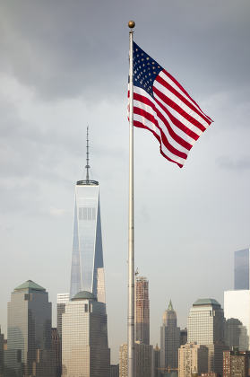 the flag of the United States in front of the skyscrapers in New York