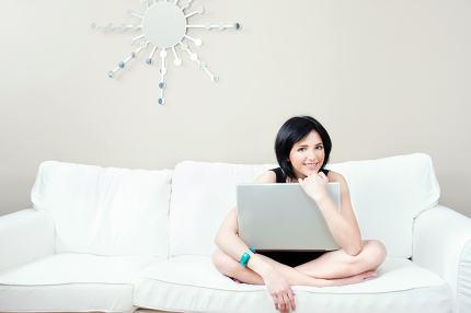 girl on white sofa with laptop