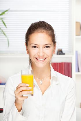 woman holding glass of orange juice