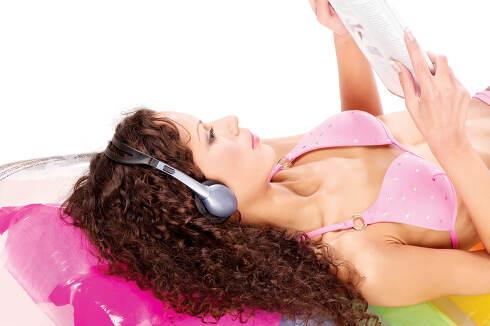 girl on air mattress reading newspaper