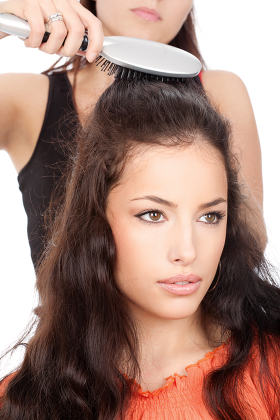 hairdresser combing woman