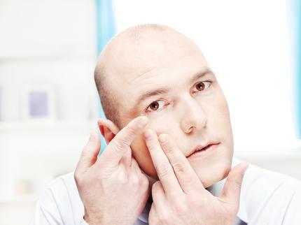 man putting contact lens in eye