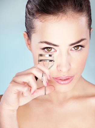 Pretty woman holding tool for eyelash