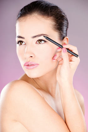 woman applying cosmetic pencil