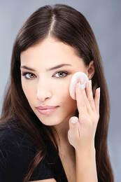 woman applying make up on cheek