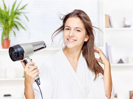 Woman drying hair at home