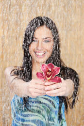 Woman hold red orchid under water drops
