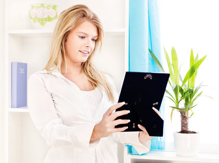 woman holding frame of photo at home