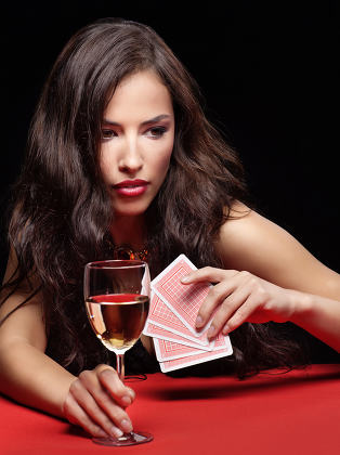 woman holding gambling cards and wine