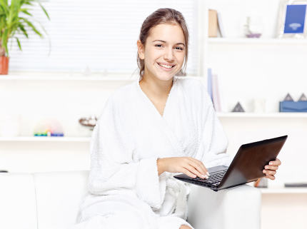 Woman in bathrobe with computer