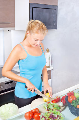 woman in kitchen cutting vegetables
