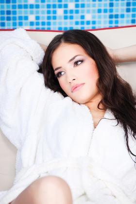 Woman in white bathrobe resting