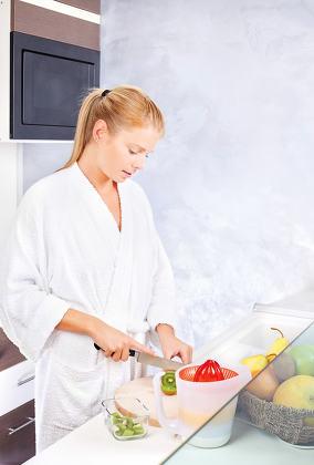 woman making fruit salad in kitchen