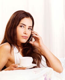 woman making phone call in bed