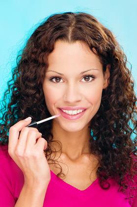 woman putting lipstick on lips