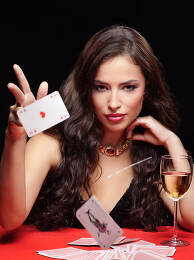 woman throwing gambling cards on red table