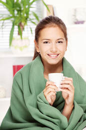 woman under blanket drinking tea