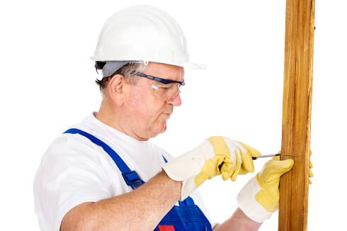 worker screwing nail in board