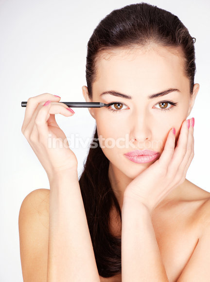 woman applying cosmetic pencil